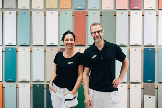 Portrait of smiling sales employees standing against multi colored wall in store