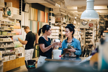 Sales woman showing paint can to customer at hardware store