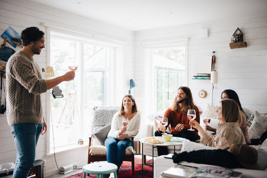 Smiling man giving speech while raising wine toast to friends during party at home