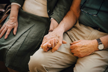 Midsection of senior couple holding hands sitting at nursing home