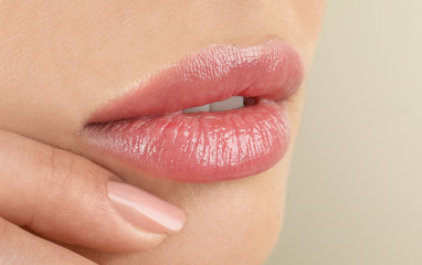 Woman with beautiful full lips on beige background, closeup Wall mural