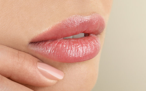 Woman with beautiful full lips on beige background, closeup