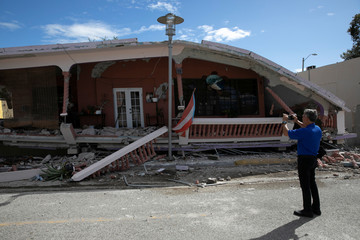A man uses his phone to take photos of a house that collapsed on its foundation after an earthquake in Guanica