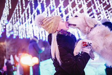 Devotion of dog, Labrador Retriever licks kisses mistress in winter in park, in background...