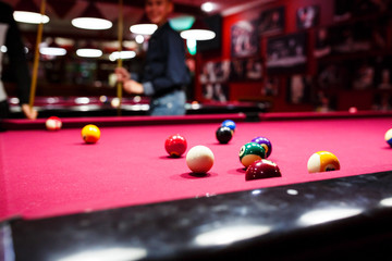 Boy plays billiard or pool in club. Young Kid learns to play snooker. Boy with billiard cue strikes the ball on table. Active Leisure, sport, hobby concept