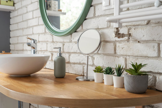 Bathroom in modern style with wooden counter, ceramic wash basin, round mirror, brick wall and succulents. Scandinavian design and minimalism in apartment.