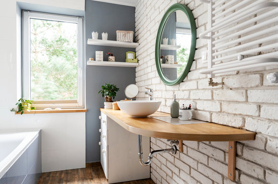 Bright interior of bathroom with window, wooden furniture and counter, round mirror and white brick wall. Simple and stylish design in scandinavian style.