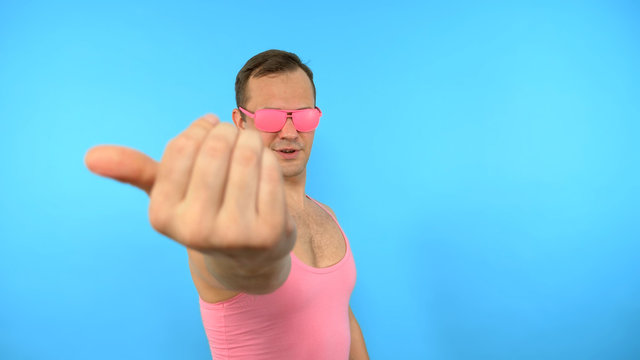 crazy man in pink glasses come here gesture on blue background