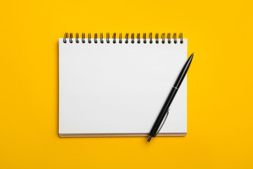 Photo sur Plexiglas Spirale Open notebook and pen on yellow background, top view