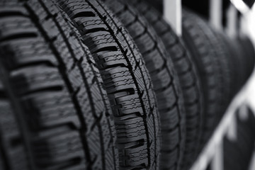 Car tires on rack in auto store, closeup