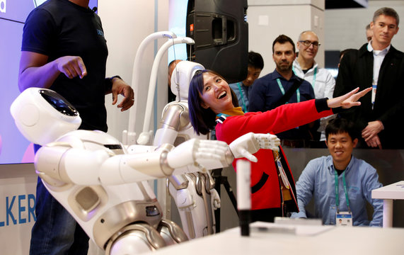 Tanli Yang, a journalist with China Global Television Network, performs yoga poses with Walker, an intelligent humanoid service robot, at the UB Tech booth during the 2020 CES in Las Vegas