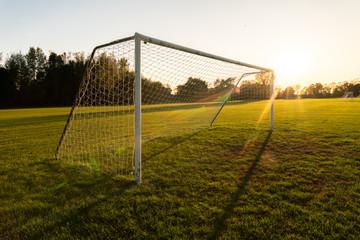 An empty soccer goal at sunset