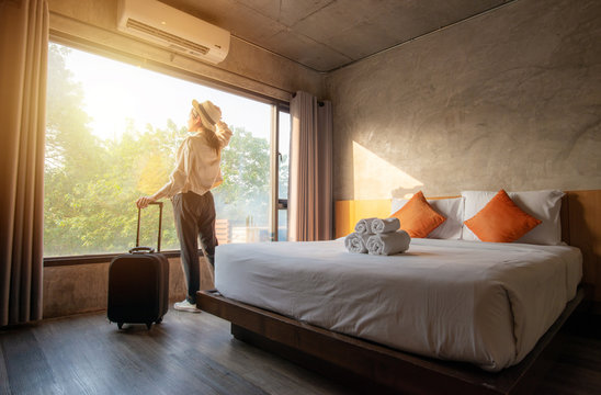 Tourist woman with her luggage in hotel bedroom.