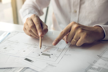 Engineering man showing blueprint detail for people buying house.