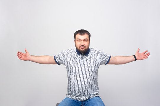 A man warmly greets the viewer with his arms spread wide over a white background.