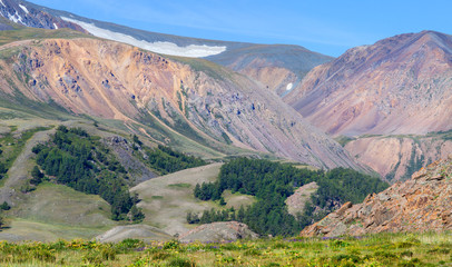 Fototapete - Mountain view. Snow on top, colored rocks, forest.