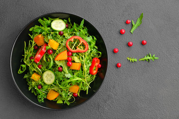 Plate with tasty salad on grey background