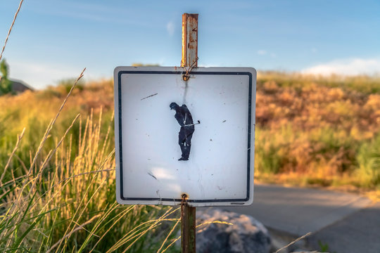 Focus on a weathered sign at a golf course against road and grassy land