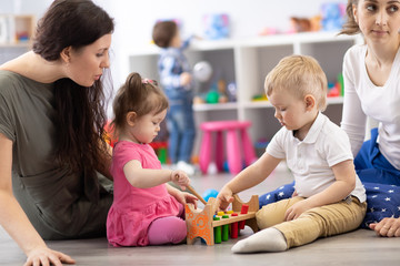 Children playing in kindergarten or daycare centre under the supervision of moms