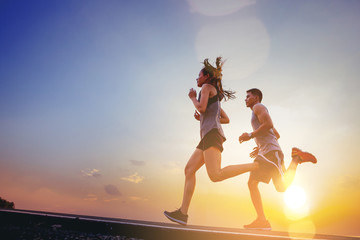 Young couples running sprinting on road. Fit runner fitness runner during outdoor workout with...