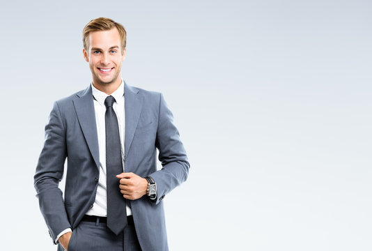 Portrait of happy smiling young businessman in confident suit, on grey background. Business success concept.