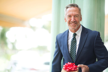 Mature handsome man giving a gift stock photo