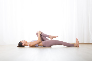Fotomurales - Portrait of gorgeous active sporty young woman practicing yoga in studio. Beautiful girl practice Pavana Muktasana, wind removing yoga pose. Healthy active lifestyle, working out indoors in gym.