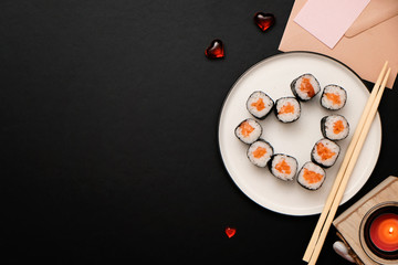 Foto op Aluminium Sushi bar Sushi for Valentines Day - roll in heart shape, on plate on black background. Flat lay. Space for text.