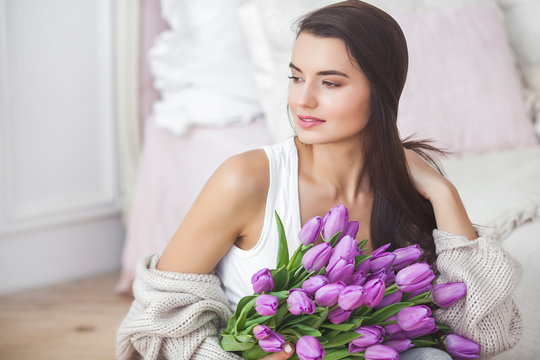 Attractive young woman with flowers indoors in the bedroom. Portrait of beautiful lady at home. Close up shot of female with tulips.