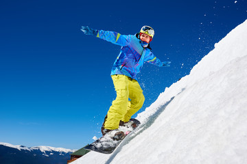 Snowboarder man riding snowboard fast down steep snowy mountain slope, jumping in air on copy space background of blue sky and white snow on sunny winter day. Extreme sport and recreation concept.