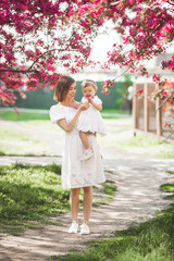 Young loving mother walking with her little baby on spring background. Cute child and her mom outdoor.Family in the park.