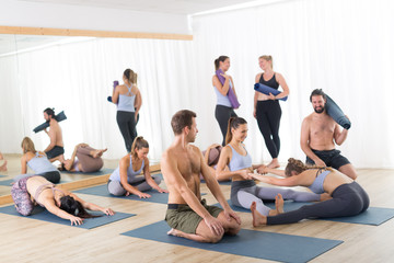 Group of young sporty attractive people in yoga studio, relaxing and socializing after hot yoga class. Healthy active lifestyle, working out indoors.