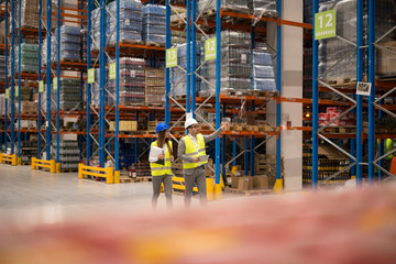 Positive cheerful warehouse workers checking organization and distribution of products in large storage area. Teamwork at warehouse. Wall mural