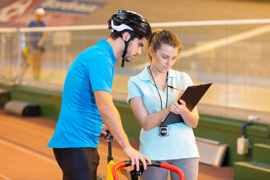 female coach talking to male cyclist in indoor track
