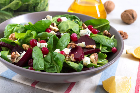 Salad with young spinach, boiled beets, blue cheese, nuts, cranberries in a bowl on a light background. Tasty diet fitness dish. Vitamin salad. Proper nutrition