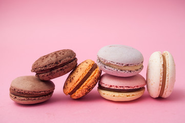 Closeup of french macarons pile on pink background