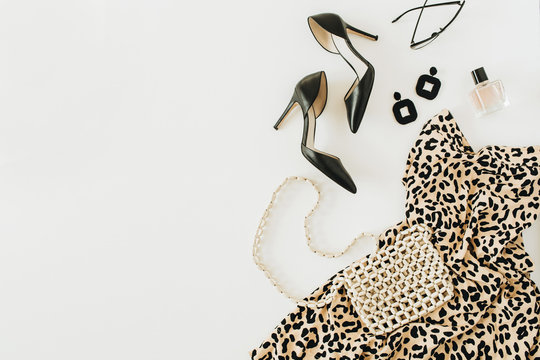 Modern fashion collage with female clothes and accessories. Leopard print dress, high-heel shoes, earrings, glasses, purse, perfume on white background. Flat lay, top view.