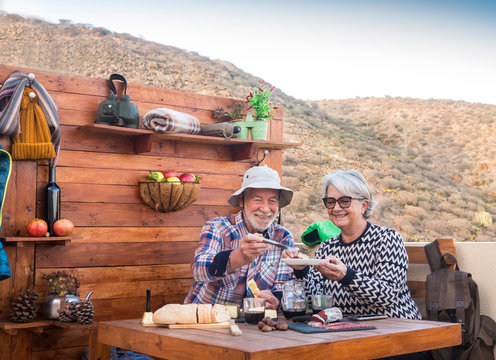 Two cheerful senior people enjoy a break with food and drinks after a hike in the mountains. Wooden table outdoors with cheeses, salami and red wine. 70 year old couple with white hair