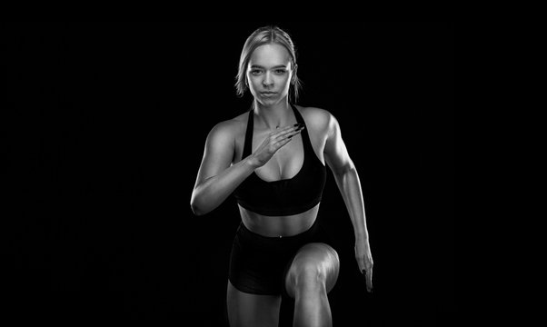 Woman sprinter and fit athlete runner running on the black background. The concept of a healthy lifestyle and sport. Woman in black and white sportswear.