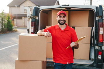 Image of delivery man holding clipboard while standing with boxes