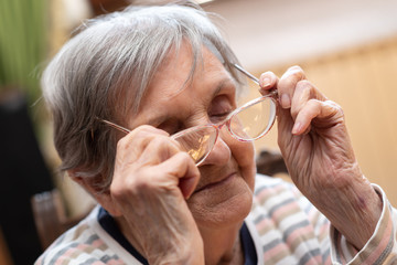Senior woman putting on eyeglasses