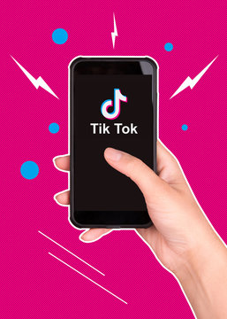 Tik Tok application icon on smartphone screen close-up.  A smartphone in the hands of a girl who uses the Tik Tok application.