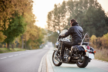 Back view of bearded biker with long hair in black leather jacket sitting on cruiser motorcycle, on blurred background of straight road stretching to horizon and golden autumn trees in the evening.