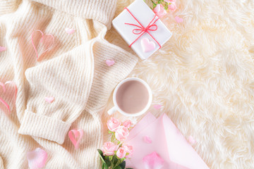 Pink paper hearts with gift box and roses, coffee cup on , beige sweater on cream colour knitted blanket and fluffy background. Love and Valentine's day during Winter concept.