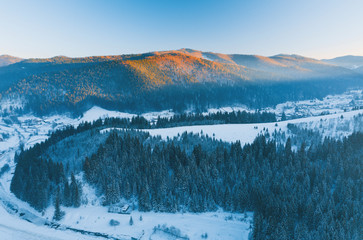 Fototapeta Drone photo of winter river and forest in the mountains during sunset