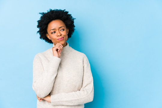 Middle aged african american woman against a blue background isolated looking sideways with doubtful and skeptical expression.