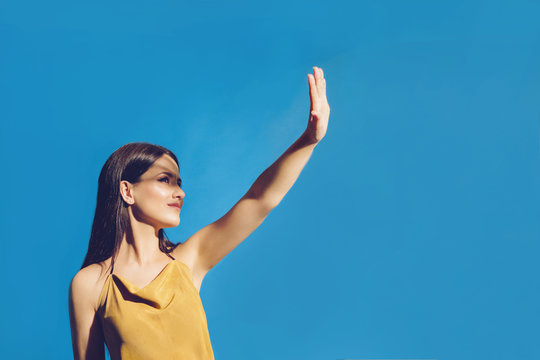 Portrait of young girl covering her face to block sun light. Shadow and light over woman's face. Creative portraits. Female in orange summer beach dress on a blue background