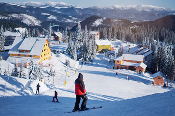 Fototapeta Snowy mountains and ski lifts. Skiers and snowboarders skiing downhill to village. obraz