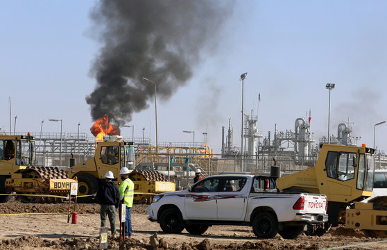 Workers are seen at West Qurna-1 oil field, which is operated by ExxonMobil, in Basra