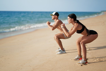 Poster Jogging Healthy lifestyle. Young beautiful couple doing sports exercises at the beach.